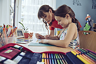 Mother helping girl doing her schoolwork at home - MFF03713