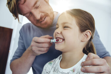 Father brushing daughter's teeth in bathroom - MFF03734