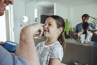 Father putting facial cream on daughter's face - MFF03743
