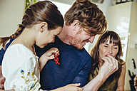 Parents and daughter tasting redcurrants - MFF03749