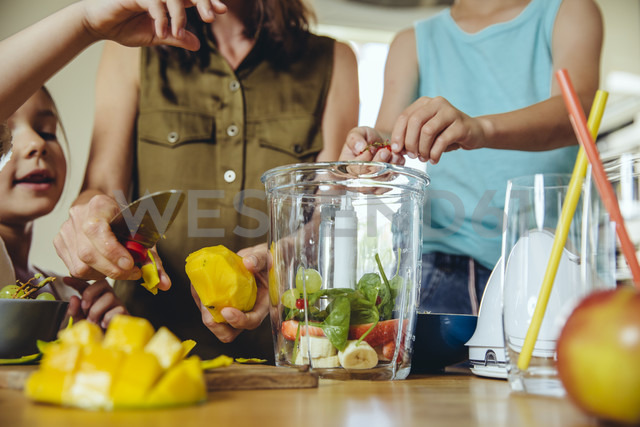 Mother and children putting fruit into a smoothie blender - MFF03752