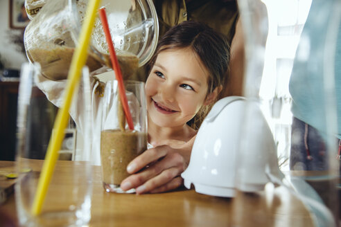 Girl pouring smoothie into glass with mother's help - MFF03758