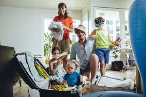 Happy family of five packing for holiday trip - MFF03779