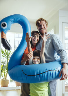 Happy parents with son holding an inflatable flamingo at home - MFF03782