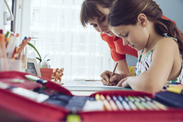 Mother helping girl doing her schoolwork at home - MFF03785
