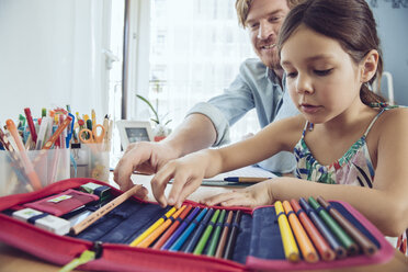 Father helping girl doing her schoolwork at home - MFF03788