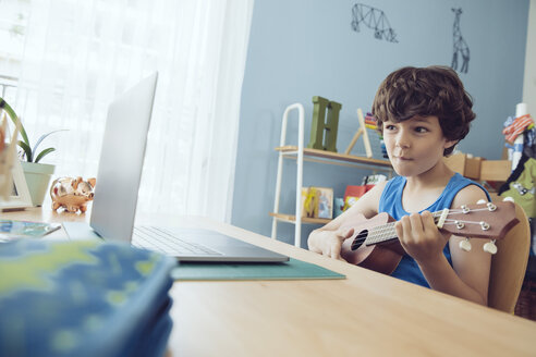 Boy using laptop to play a song on an ukulele - MFF03791