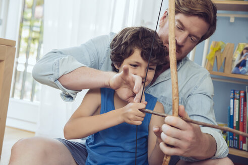 Father showing son how to use self-made bow and arrow - MFF03803