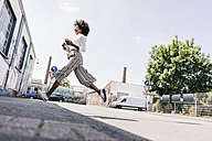 Vital young woman crossing the street - KNSF02254