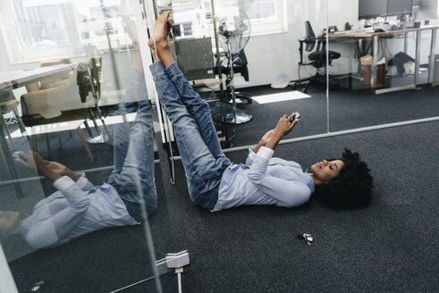 Young woman lying on the floor in office checking cell phone - KNSF02281