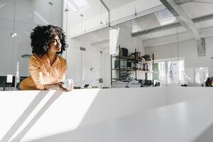 Young woman having a coffee break in office - KNSF02293
