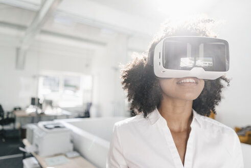 Woman wearing VR glasses in office - KNSF02305