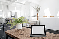 Tablet on wooden table in office - KNSF02344