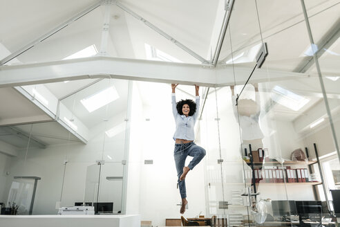 Young woman hanging on beam in office - KNSF02350