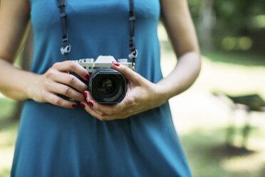 Woman's hands holding analogue camera, close-up - MOMF00220