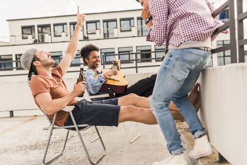 Three friends having a rooftop party - UUF11452