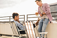 Young couple with beer and guitar on a rooftop party - UUF11455