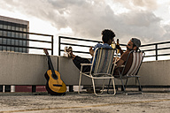 Young couple with beer and guitar sitting on rooftop - UUF11464