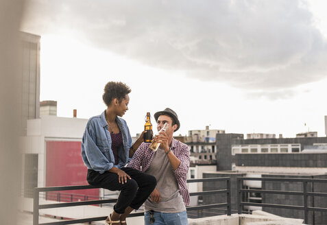 Young couple clinking beer bottles on rooftop - UUF11470