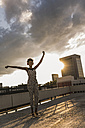 Young woman with headphones dancing on rooftop - UUF11485
