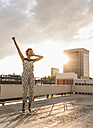 Young woman with headphones dancing on rooftop - UUF11488