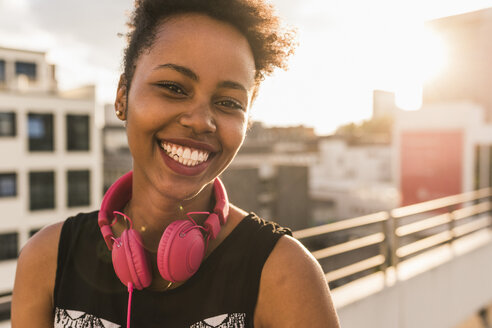 Portrait of happy young woman with headphones on rooftop - UUF11491