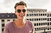 Portrait of happy young man on rooftop - UUF11512