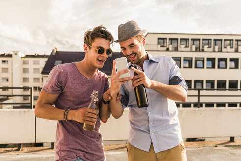 Two friends with beer bottles and cell phone on rooftop - UUF11515