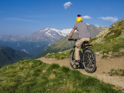 Italy Lombardy, Passo di Val Viola, Man riding e-bike in the mountains with action cam on his helmet - LAF01860
