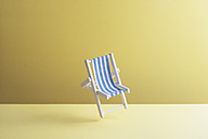 Single beach chair hovering in the air in front of yellow ground, 3D Rendering - DRBF00029