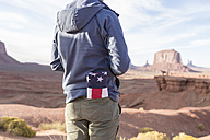 USA, Utah, back view of young man with folded American flag in his pocket at Monument Valley - EPF00456