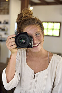Portrait of laughing young woman taking picture with camera - ECPF00051