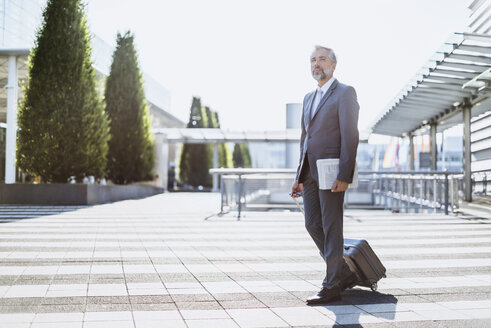 Businessman pulling rolling suitcase outdoors - DIGF02615