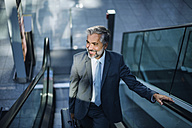 Smiling businessman on escalator - DIGF02621