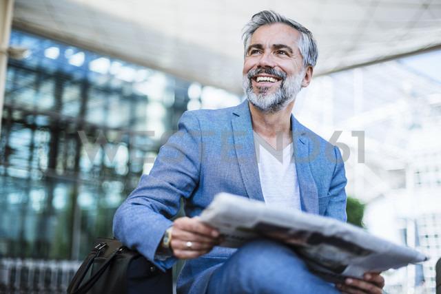 Happy businessman reading newspaper - DIGF02639 - Daniel Ingold/Westend61