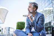 Businessman sitting outdoors thinking - DIGF02651