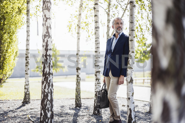 Businessman holding bag leaning against a tree - DIGF02654