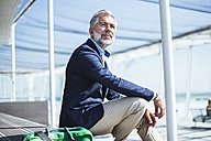 Businessman sitting outdoors with bag - DIGF02660