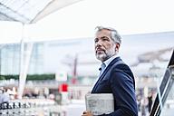 Businessman outdoors holding newspaper - DIGF02666