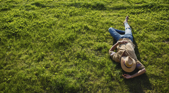 Young man sleeping on a meadow, top view - MRAF00212