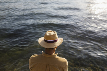 Back view of man with straw hat looking at water - MRAF00221