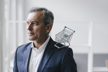 Portrait of manager with mini shopping cart - KNSF02368