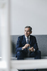 Mature businessman with glass of coffee sitting on couch in his office looking out of window - KNSF02383
