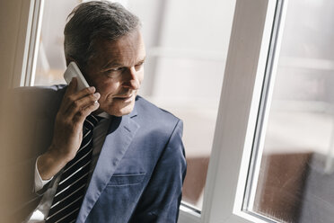 Smiling mature businessman on cell phone looking out of window - KNSF02386