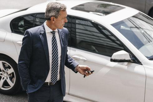 Businessman using remote control key of car - KNSF02389