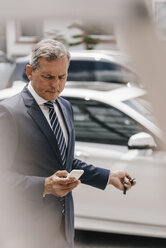 Businessman checking message while using remote control key of car - KNSF02392