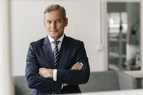 Portrait of mature businessman with arms crossed in his office - KNSF02395