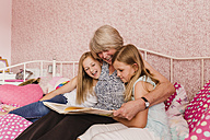 Grandmother sitting on bed with her granddaughters reading a book - NMSF00136