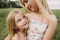 Two little sisters cuddling on a meadow - NMSF00148