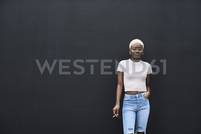 Portrait of young woman with cigarette in front of black background - IGGF00098